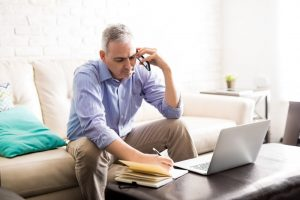 Man sits on couch while talking on the phone, learning about insurance benefits