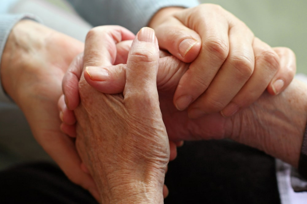 Younger person holding elderly person's hands in a comforting way