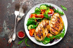 Nutritious meal with grilled chicken, tomatoes, and green salad