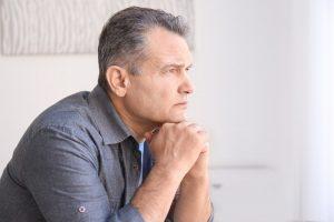 Older man sitting with hands under chin
