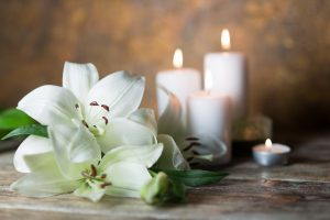 White lilies lying next to several lit white candles