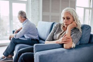 Man and wife sitting on couch, not talking to each other, angry or upset