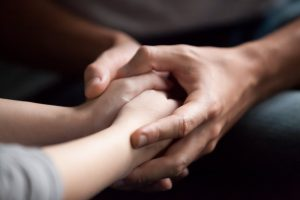 Focused on hands, man holding woman's hands in a comforting way