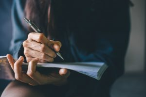 Dark-haired woman writing in notebook that is resting in her lap