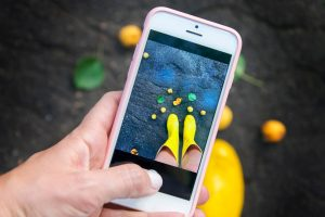 Person taking a photo of their yellow rainboots against a fall backdrop