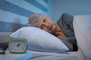 Older woman laying awake in bed in the middle of the night