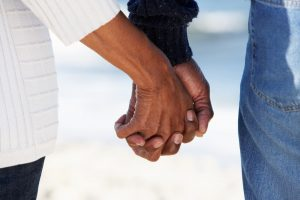 Older couple walking on beach, holding hands, focus on hands