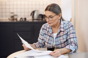 Middle-aged woman sitting at table looking at documents