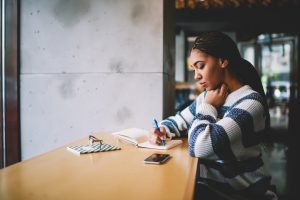 Young woman sitting at counter in coffee shop, journaling in notebook
