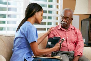 At home nurse taking blood pressure of older male patient, sitting on couch