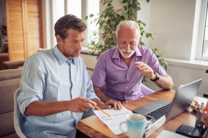 Father and adult son sitting at desk together, looking at documents with computer nearby