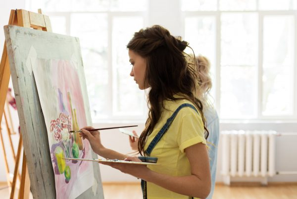 Woman standing at easel, painting on canvas