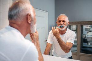 Older man looking into bathroom mirror while brushing his teeth