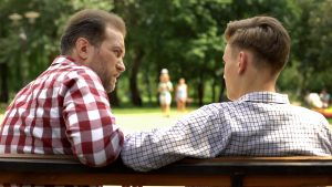 Father and son sitting on bench talking