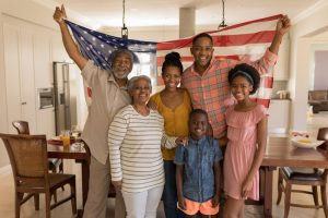 Family of 6 standing in living room, draping American flag on their shoulders