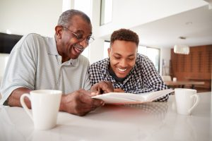 Grandfather and grandson sitting at kitchen table, looking at book together, laughing