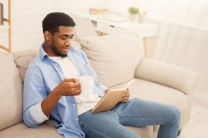 Man sitting on couch with mug and book