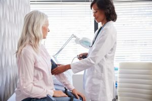 Woman visiting her doctor, getting blood pressure taken