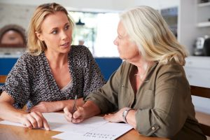 Adult daughter and mother looking at documents while sitting at table