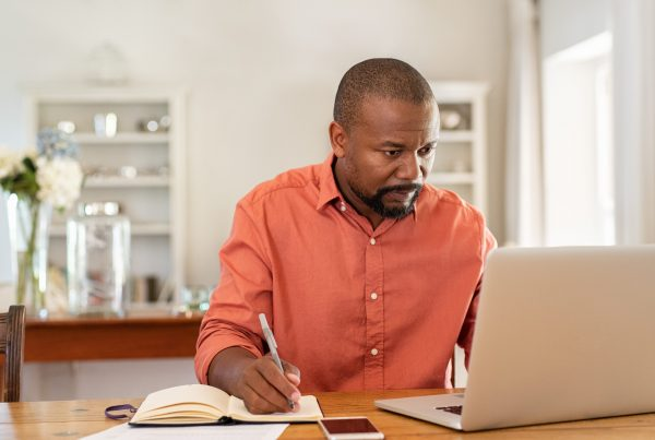 Middle-aged man sitting at computer in his bright, clean home