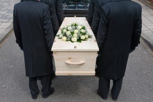 Pallbearers carrying light-colored casket with funeral spray with white roses on top