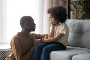 Dad talking kindly to sad young daughter