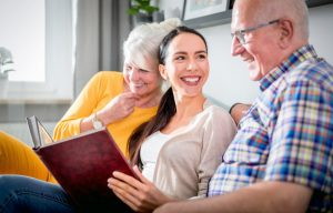 Young woman sitting with grandparents, looking at photo album and smiling