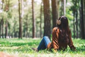 Woman sitting outside in the woods, trees and green grass, quite and contemplative
