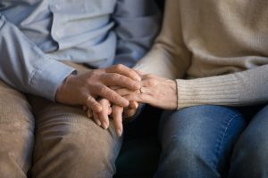 Man and woman sitting down, holding hands, focus on hands as they rest on laps
