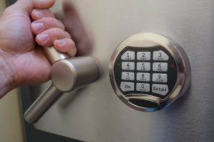focus on front of a safe with number pad, hand on lever to open