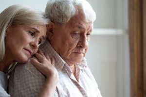 Mature woman standing behind mature man, both sad, her head resting on his shoulder