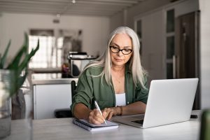 Mature woman sitting at kitchen table with laptop in front of her, writing on notepad