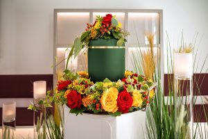 Green urn sitting in a prominent location, surrounded by yellow and red flowers