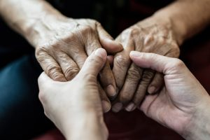 Younger person holding older person's hands, focus on hands only