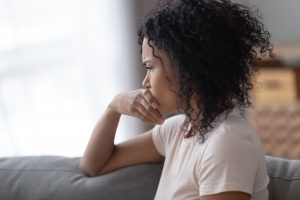 Pensive young woman sitting on couch, hand covering mouth, anxious