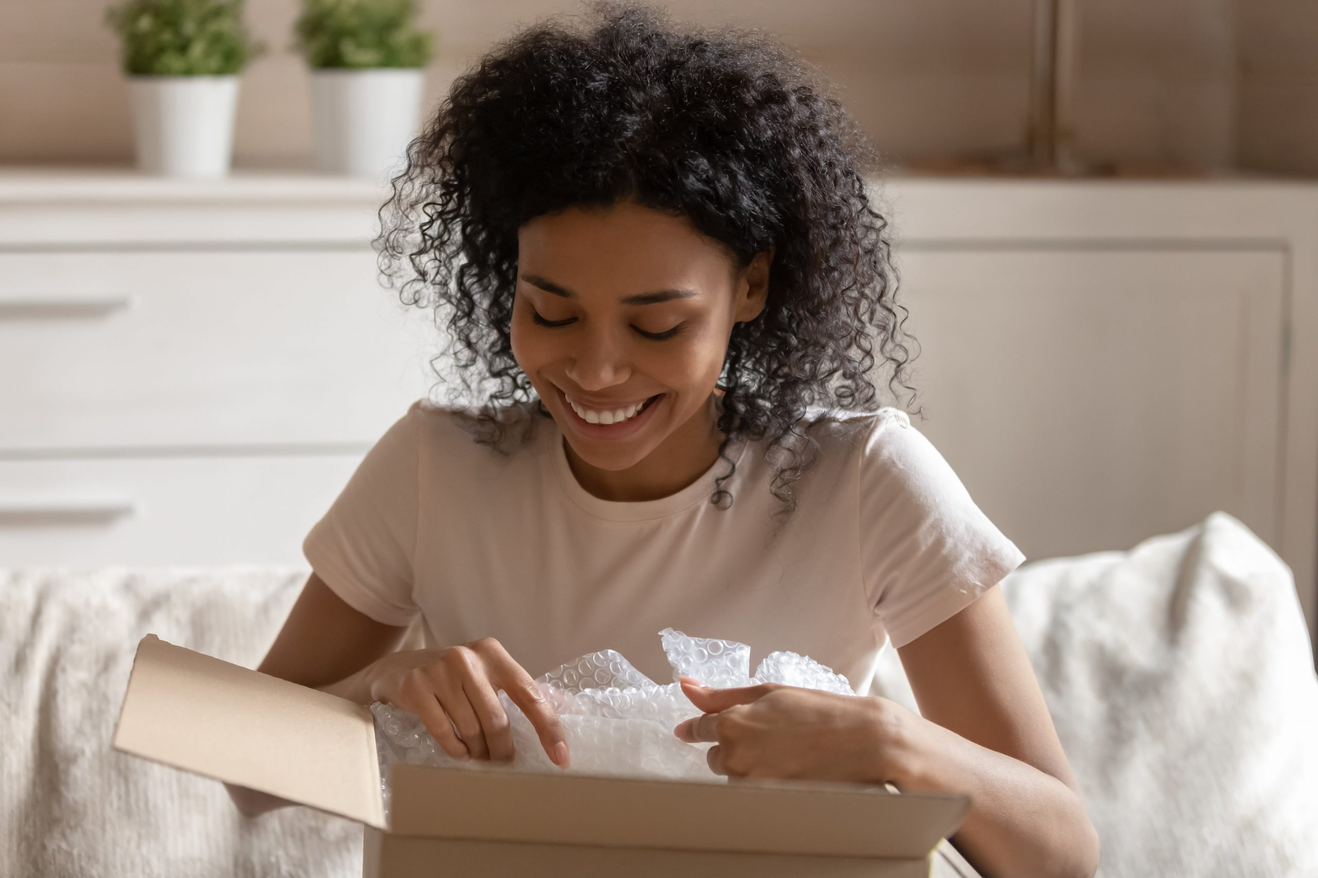 Young woman sitting on couch opening a box and smiling