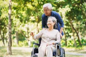 Older man pushing older woman in wheelchair, outside and smiling