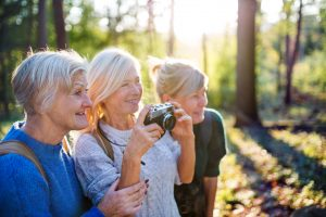 Three women in the woods, taking photographs of nature, supporting each other through friendship