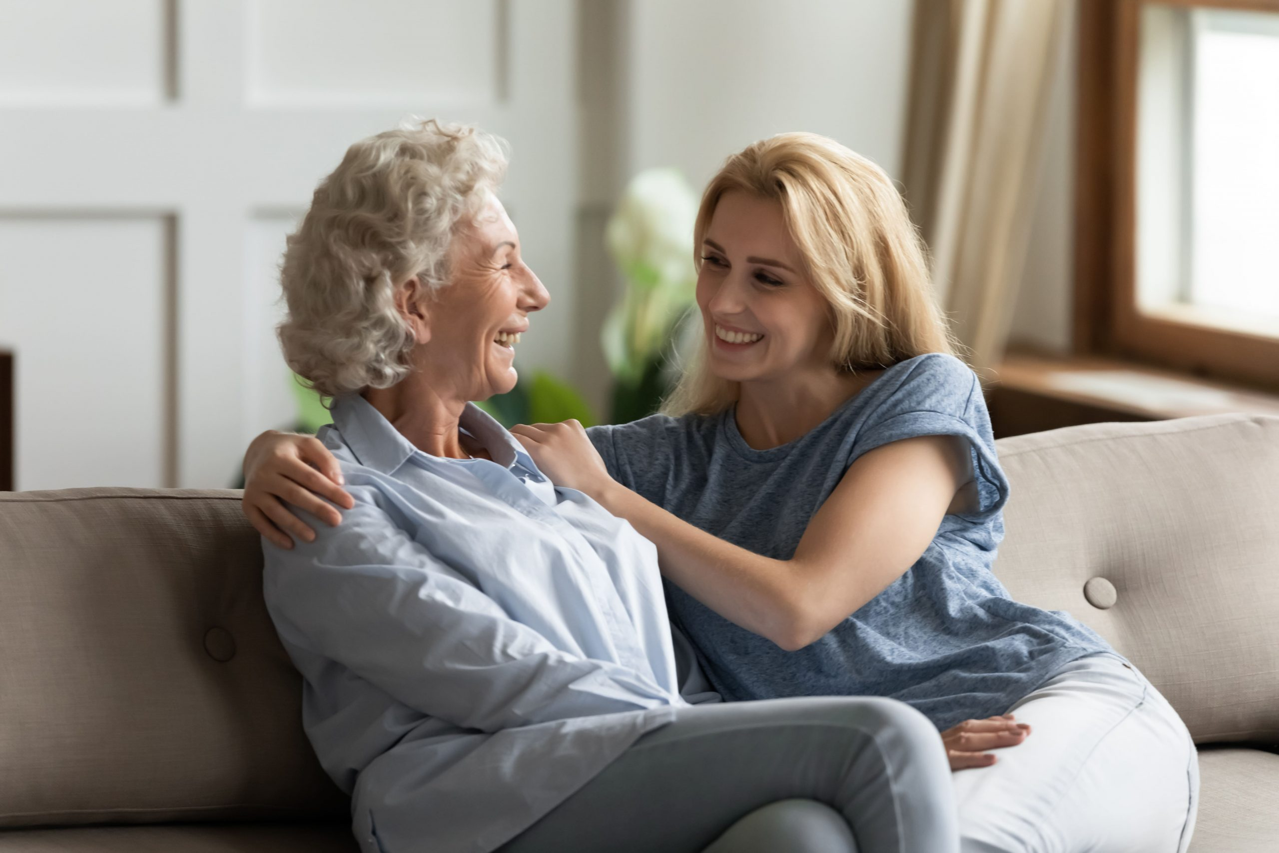 Mother and adult daughter sitting on couch talking and smiling