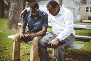 Two male friends sitting together, praying