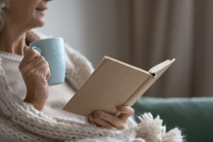 Woman sitting in chair, wrapped in a blanket with a open book and light blue mug