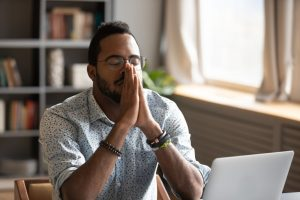 Man sitting at table with computer, eyes closed, breathing deeply