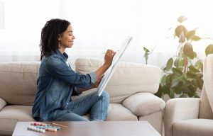 Woman sitting on couch as she draws on canvas, expressing herself