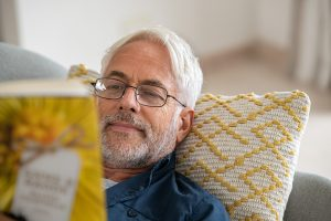 Middle-aged man laying on couch, resting on yellow checkered pillow, reading a book