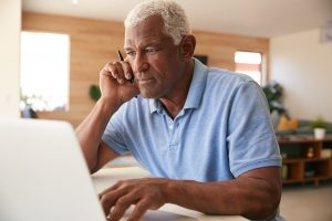 Older man on the phone while looking at computer