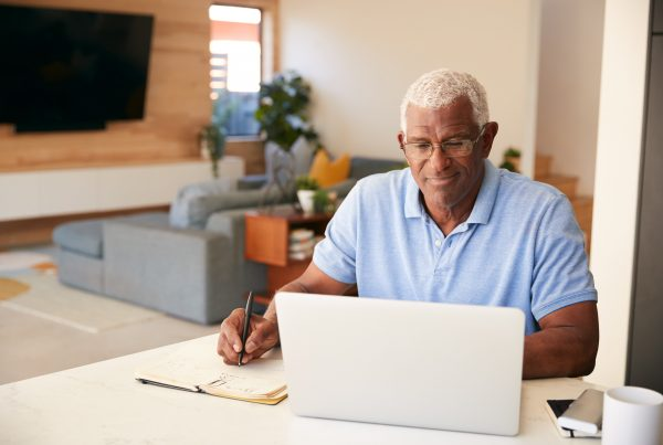 Older man sitting at computer, writing notes in notebook