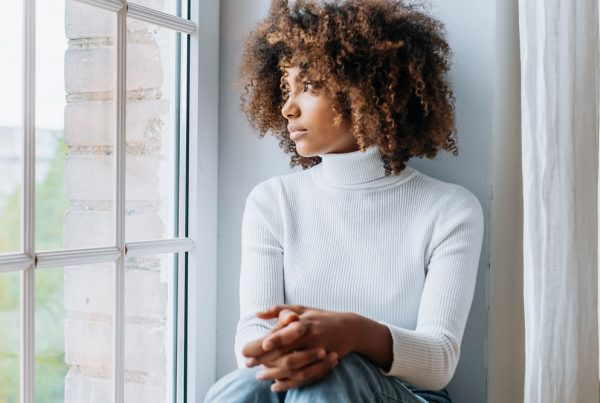 Young woman in white sweater looking out the window