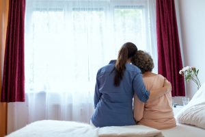 At home hospice nurse sitting with patient, giving a hug as they look out the window
