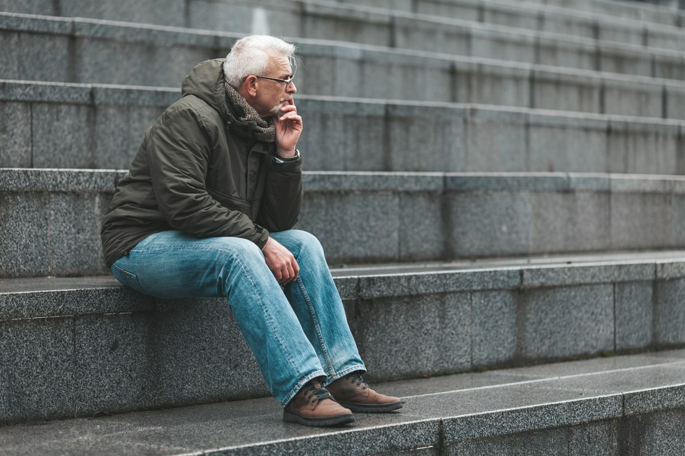Older man sitting quietly on stone steps as he thinks