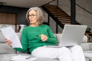 Woman sitting on couch with computer in lap, reading documents